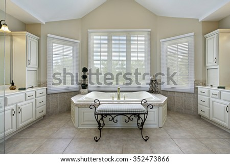 Master bath in luxury home with large bathtub - stock photo