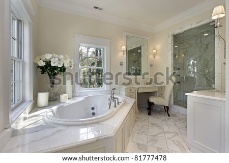 Master bath in luxury home with step up tub - stock photo