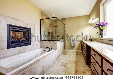 Master bathroom in modern house with fireplace, bath tub with tile trim, glass shower and modern cabinets.