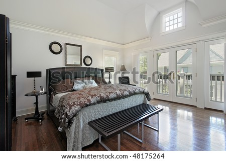Master bedroom in luxury home with balcony view - stock photo