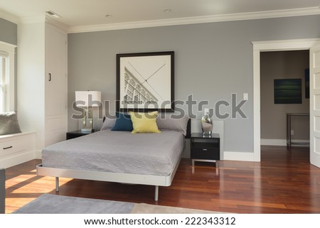 Master bedroom in luxury home with cherry wood flooring - stock photo