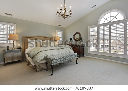 Master bedroom in luxury home with circular window - stock photo