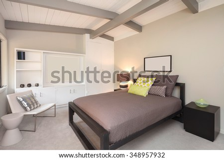 Master Bedroom in Luxury Home with white leather chair and wooden ceiling. - stock photo
