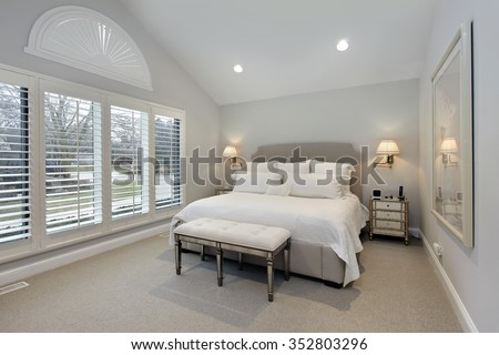 Master bedroom in suburban home with wall of windows - stock photo