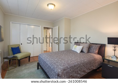Master bedroom with armchair, pillows and closet wooden floor in modern luxury home. - stock photo