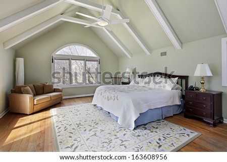 Master bedroom with ceiling beams and large window - stock photo