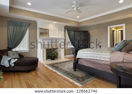Master bedroom with fireplace and rug - stock photo