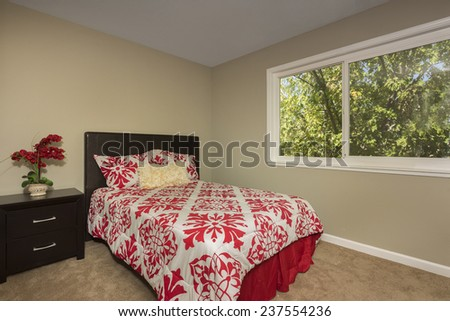 Master Bedroom with red cover. Queen sized bed with red white covers.  - stock photo