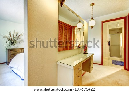 Master bedroom with wall separated bed from bathroom. View of bedroom vanity with drawers and mirror - stock photo