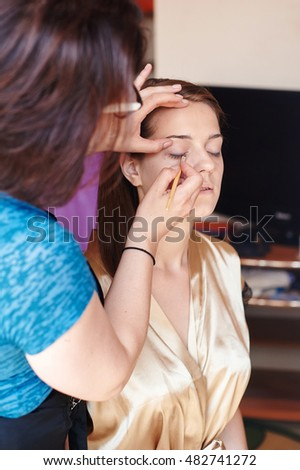 Master doing make up for young beautiful bride