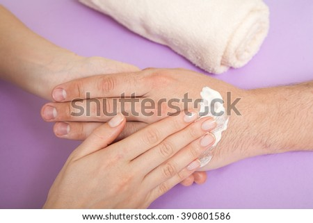 master doing manicure for man in beauty salon - stock photo