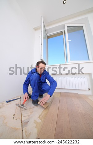 Master in blue overalls laid wood parquet in white room - stock photo