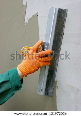 Master makes plaster on a wall - stock photo