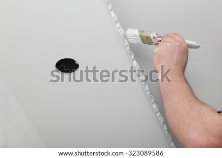 Master renovating house interior. Painting the ceiling with a brush with paint - stock photo