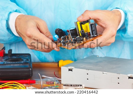 Master servicing electronic hardware in the service workshop - stock photo