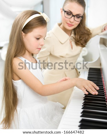Master teaches little girl to play piano. Concept of music study and creative hobby - stock photo