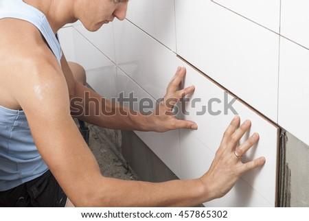 master tiler glues wall white ceramic tiles - stock photo