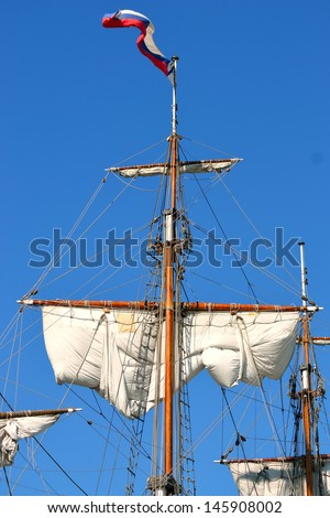 Masts and sails, old sailing ship on the sky background. - stock photo