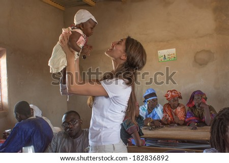 MATAM,SENEGAL-CIRCA NOVEMBER 2013:Caterina Murino plays with an African child,Caterina Murino is the testimonial of the NGO AMREF,circa November 2013.  - stock photo