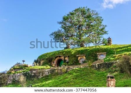 MATAMATA, NEW ZEALAND - JULY 24, 2012: Hobbit houses in Lord of the Rings location Hobbiton, Matamata, New Zealand - stock photo