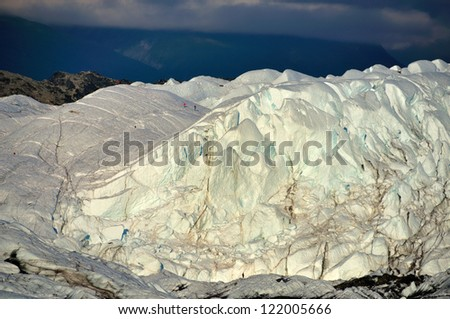 Matanuska glacier with tiny looking people on it and dark clouds in the background. - stock photo