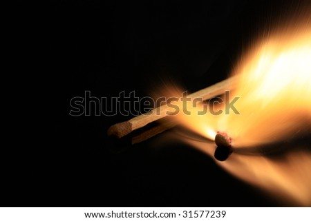 Match burning, isolated on black reflective surface