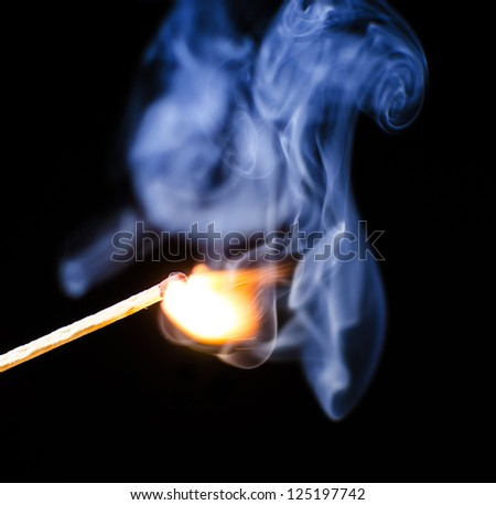 Match ignition with smoke over black background