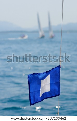 Match race with flag blue Peter in foreground  - stock photo