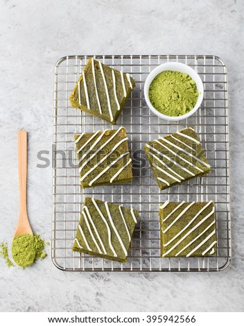 Matcha green tea brownie cake with white chocolate on a cooling rack Grey stone background Top view Copy space - stock photo