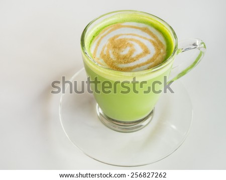 Matcha green tea latte beverage in glass mug on white table. - stock photo