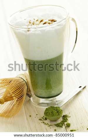 Matcha green tea latte beverage in glass mug with whisk - stock photo