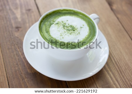 Matcha green tea latte beverage in glass on table. - stock photo