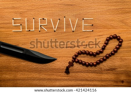 "Matches and combat knife and rosary with cross on wooden table. Matches form the word ""SURVIVE"""