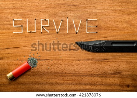 """Matches with combat knife and open cartridge from a shotgun from which the powder on wooden table. Matches form the word """"SURVIVE"""" - stock photo"""
