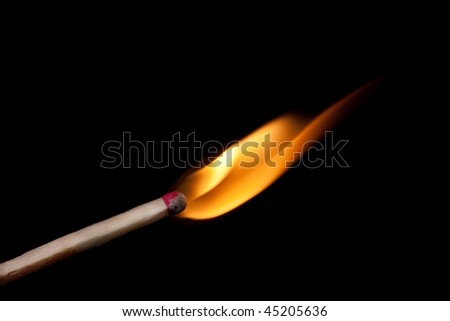 Matchstick and flame against black background
