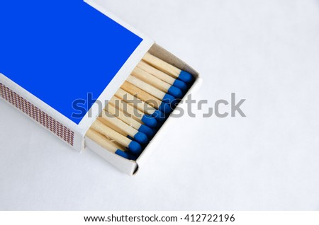 Matchstick in blue box on white isolated background - stock photo