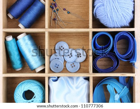 Material for sewing in wooden box closeup - stock photo