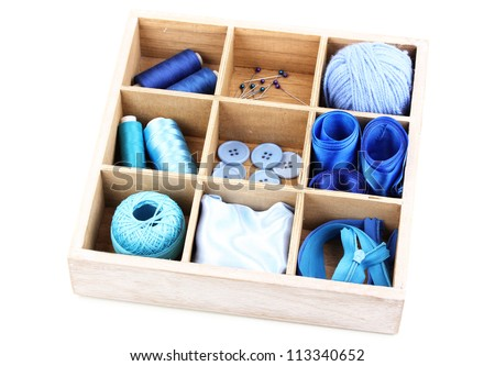 Material for sewing in wooden box isolated on white