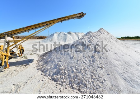 Materials handling equipment and conveyor belts work amid piles of borax near an agricultural chemical plant. - stock photo