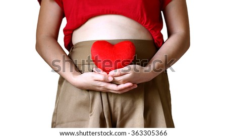 maternity concept : pregnant woman touching her bare tummy and holding in hands of red heart - stock photo