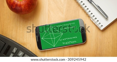 Math problems against smartphone on desk - stock photo