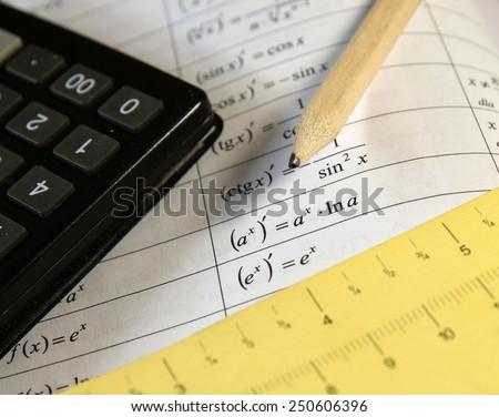 Math study for the exam set (book, pencil, calc) - Background shows trigonometry formulas - stock photo