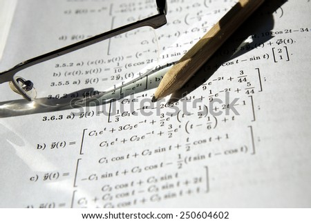 Math study for the exam set (book, pencil, glasses) - Background shows differential equations, derivative and integral