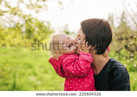 mather kissing her daughter. family outdoor - stock photo