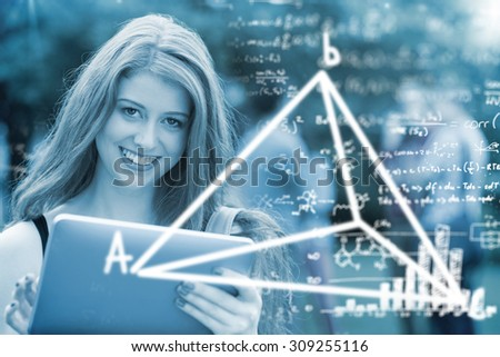 Maths equations against pretty student smiling at camera using tablet pc - stock photo