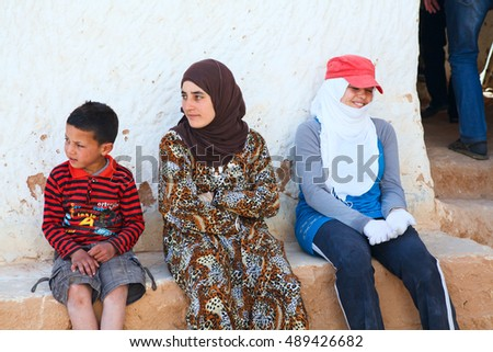 MATMATA, TUNISIA, AFRICA-CIRCA MAY, 2012: Family of berbers sits in typical yard of an underground house of troglodytes. Cave-dwellers Berbers living.