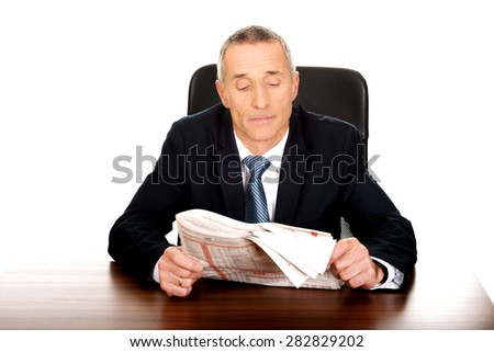 Matre businessman reading a newspaper in the office. - stock photo