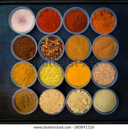 Matrix of colorful spices in round bowls.