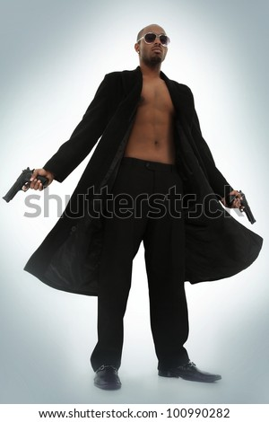 Matrix Style Role Play Character Adult Man in Trench Coat with Pistols over blue foggy background - stock photo