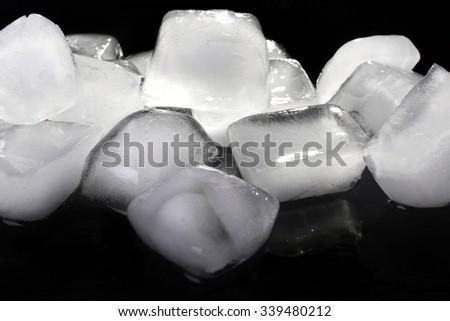 Matted ice cubes on dark liquid background - stock photo